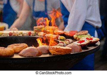 Process of preparing fish burgers at outdoor street food festival - close up