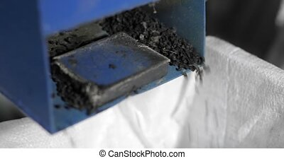 Process of recycling car tires, rubber crumbs falling from machine on plant, closeup view. Rubber processing factory. Recycled automobile tyres. Crumb rubber granulate obtained.