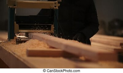 Process of sawing a board with a chain saw, industrial...