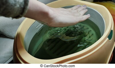 Process paraffin treatment of female hands in beauty salon....