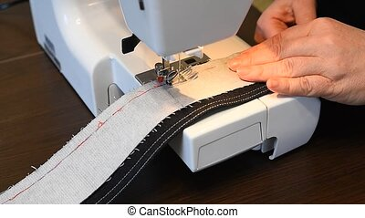 Processing details of clothes on a sewing machine close up