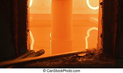 Processing glass into an oven - A steady shot of a burning...