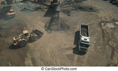 Processing of mining natural resources. Bulldozer and truck near mining machine.