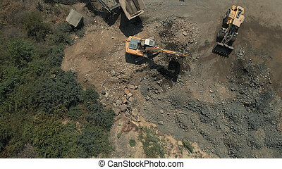 Processing of natural resources. Topview of yellow excavators picking up soil and stones.
