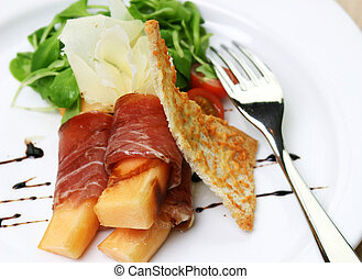 Procuitto ham rolled around fresh melon. Drizzled with...