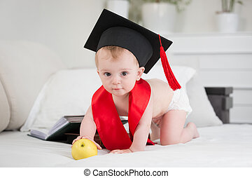 Prodigy baby in graduation cap reaching for apple