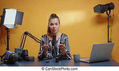 Video blogger making a product comparison between two types of NP-F batteries. Content creator new media star influencer on social media talking professional video photo equipment for online internet web show