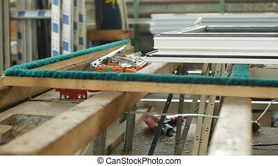 Production and manufacturing of plastic windows pvc, on the table lies the sash window, screwdriver, the shop is finished products windows, industry
