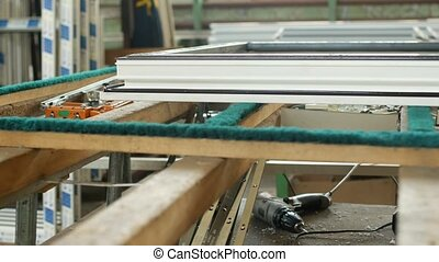 Production and manufacturing of plastic windows pvc, on the table lies the sash window, screwdriver, the shop is finished products windows, pvc