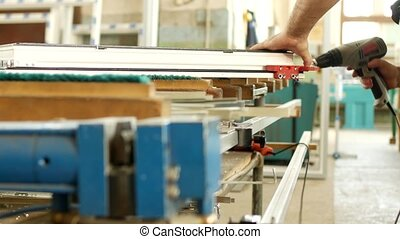 Production and manufacturing of pvc windows, a male worker...