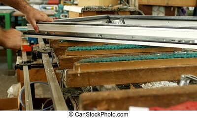Production and manufacturing of pvc windows, male worker produces pvc window assembly collects sash windows, pvc profile