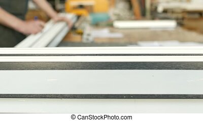 Production and manufacturing of pvc windows, the worker marks the size with a plastic pvc profile marker