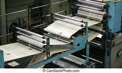Production line - Black-and-white newspaper sheets moving...