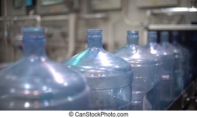 Many large plastic bottles on the conveyor. Production