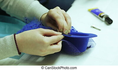 Production of ladie hat - The girl is clinging a hairpin to...