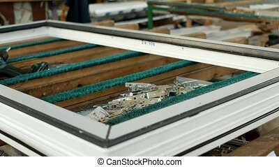 Production of pvc windows, on the table lie screws and curtains for PVC windows and screwdriver, manufacturing of frames and windows from plastic profiles, close-up, production