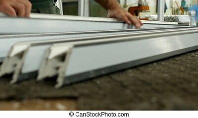 Production of pvc windows, the worker screws a metal profile...