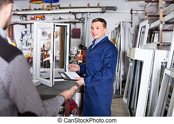 Production worker in coverall demonstrating different PVC windows to customer