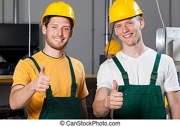 Production workers showing thumbs up sign