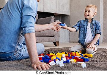 Productive intelligent boy enjoying a creative game with grandpa