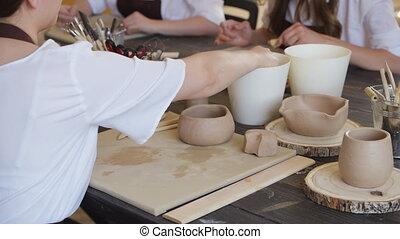 produits, table, workshop., potier, mains, maîtres, argile, haut, céramique, femme, pendant, processus, fin, rouler, fonctionnement