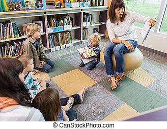 prof, livre lecture, à, enfants, dans, bibliothèque