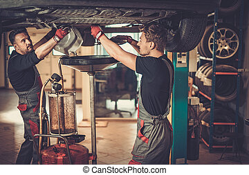 Profecional car mechanic changing motor oil in automobile...