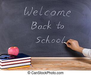 profesor, escritura, bienvenida, back to la escuela, en, erased, negro, pizarra, con, escritorio, y, suministros, en frente