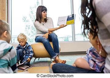 profesor, libro de lectura, a, estudiantes, en, biblioteca