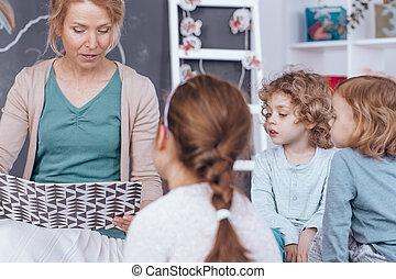 profesor, libro de lectura, en, jardín de la infancia