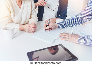 Professioanl real estate agent working with pleasant elderly couple
