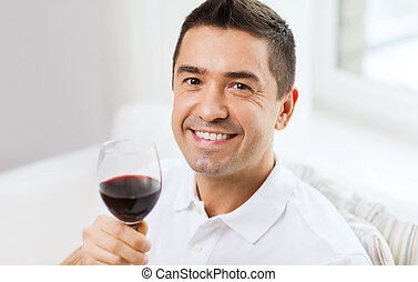 happy man drinking red wine from glass at home - profession...