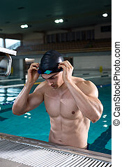 Professiona swimmer setting up his goggles for the training...