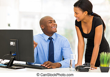 african manager with businesswoman working on computer