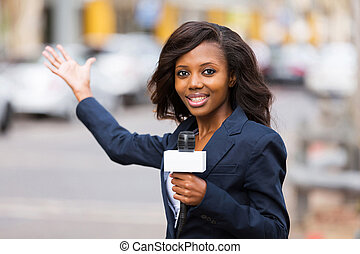 african news reporter in live broadcasting on street - ...