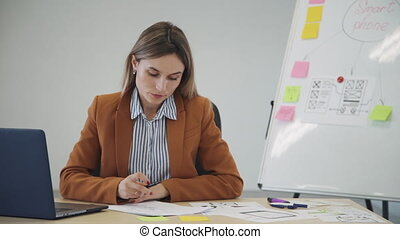 Woman creating new mobile app project and making notes on...
