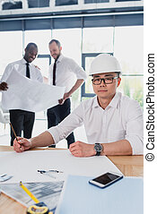 professional architects in formal wear working with blueprints at modern office, businessmen group