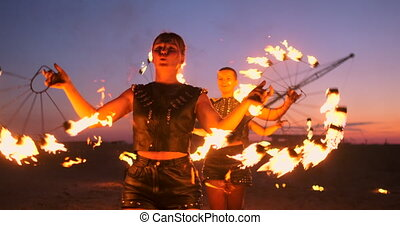 Professional artists show a fire show at a summer festival on the sand in slow motion. Fourth person acrobats from circus work with fire at night on the beach.