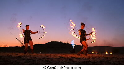Professional artists show a fire show at a summer festival...