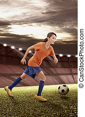 Professional asian female soccer player in action with the ball