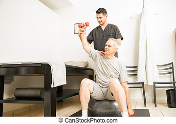 Professional Assisting Patient In Lifting Weights In Physiotherapy Clinic
