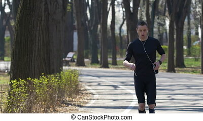 Professional athlete with smartphone and hands free checking fitness trackers while resting