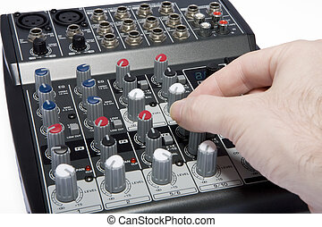 A professional audio / disk jockey / karaoke mixer on a white background with a hand adjusting the control