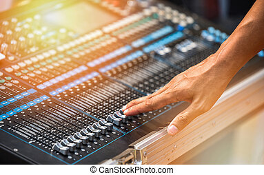 Professional audio mix sound control panel console with hand / Sound technician and lights equipment