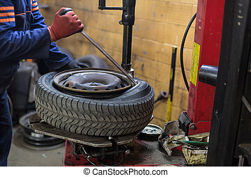 Professional auto mechanic replacing tire on wheel in car...