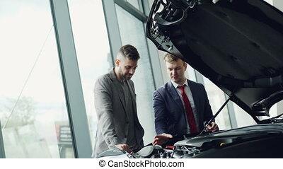 Professional automobile salesman is demonstrating customer...