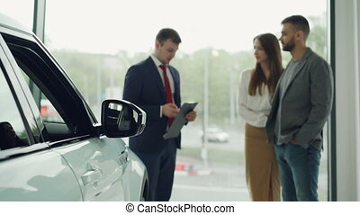 Professional automobile seller in suit is having conversation with attractive rich couple telling them about new car model, cheerful buyers are smiling. Focus on beautiful auto.