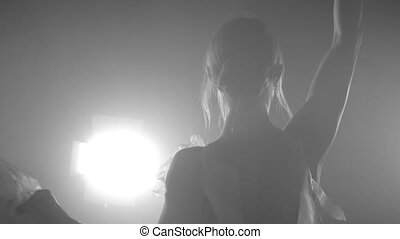 Professional ballerina dancing ballet in spotlights in dark classroom. Beautiful caucasian young girl wearing white tutu dress. Black white vintage retro effect tonned. Slow motion.