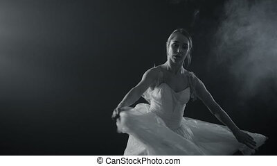 Professional ballerina dancing ballet in spotlights on big stage. Beautiful caucasian young girl wearing white tutu dress. Black and white vintage retro effect tonned
