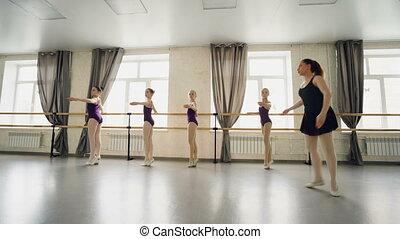 Professional ballet teacher is teaching little girls to turn...